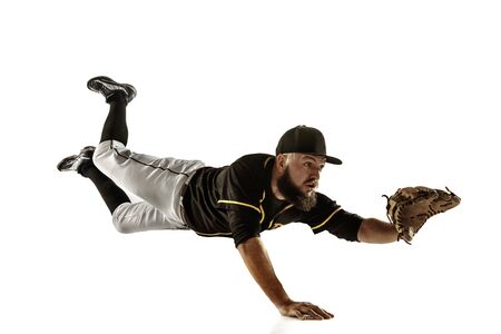 In flight. Baseball player, pitcher in black uniform practicing and training isolated on white background. Young professional sportsman in action and motion. Healthy lifestyle, sport, movement concept.