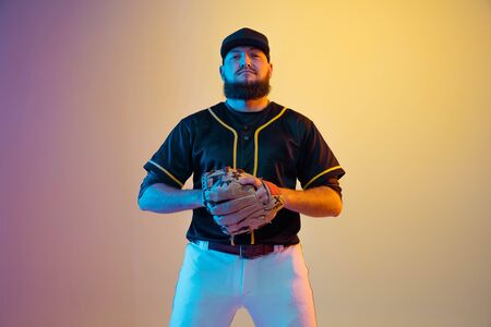 Baseball player, pitcher in a black uniform practicing and training on gradient background in neon light. Young professional sportsman in action and motion. Healthy lifestyle, sport, movement concept.