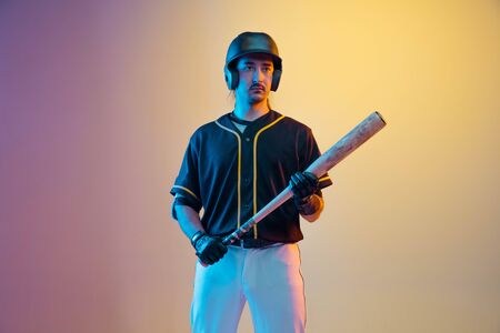 Baseball player, pitcher in a black uniform posing confident on gradient background in neon light. Young professional sportsman in action and motion. Healthy lifestyle, sport, movement concept.