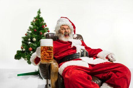 Święty Mikołaj pije piwo w pobliżu choinki, gratulując, wygląda na pijanego i szczęśliwego. Kaukaski model mężczyzna w tradycyjnym stroju. Nowy Rok 2020, prezenty, święta, zimowy nastrój. Miejsce na reklamę. Zdjęcie Seryjne