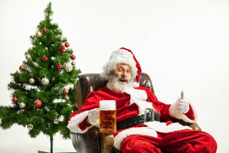 Santa Claus drinking beer near the Christmas tree, congratulating, looks drunk and happy. Caucasian male model in traditional costume. New Year 2020, gifts, holidays, winter mood. Copyspace for your ad.