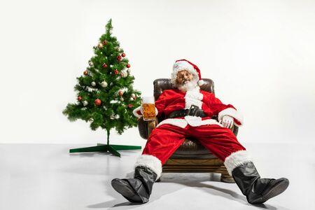 Le Père Noël boit de la bière près de l'arbre de Noël, se félicite, a l'air ivre et heureux. Modèle masculin de race blanche en costume traditionnel. Nouvel An 2020, cadeaux, vacances, ambiance hivernale. Copyspace pour votre annonce.