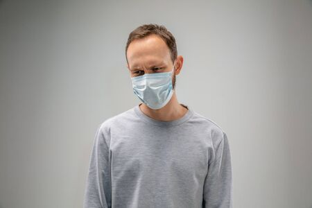 Caucasian man wearing the respiratory protection mask against air pollution and dust particles exceed the safety limits. Healthcare, environmental, ecology concept. Allergy, headache.