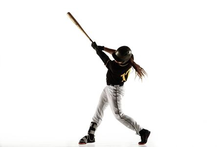 Baseball player, pitcher in a black uniform practicing and training isolated on a white background. Young professional sportsman in action and motion. Healthy lifestyle, sport, movement concept. Imagens