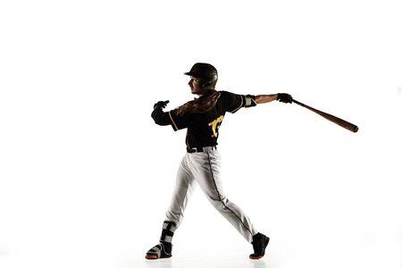 Giocatore di baseball, lanciatore in un'uniforme nera che pratica e si allena isolato su uno sfondo bianco. Giovane sportivo professionista in azione e movimento. Stile di vita sano, sport, concetto di movimento. Archivio Fotografico