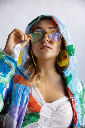 Woman wearing plastic on white background. Female model in clothes and shoes made of garbage. Fashion, style, recycling, eco and environmental concept. Too much pollution, were eating and taking it. Imagens - 134839454