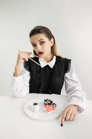We are what we eat. Womans eating sushi made of plastic, eco concept. There is so much polymers then were just made of it. Environmental disaster, fashion, beauty, food. Loosing organic world. Stock Photo