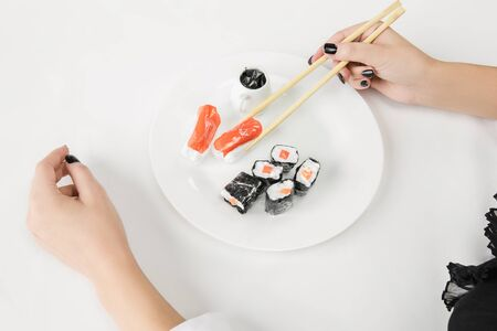 We are what we eat. Close up of female hands with plastic sushi, eco concept. There is so much polymers then were just made of it. Environmental disaster, fashion, beauty. Loosing organic world.