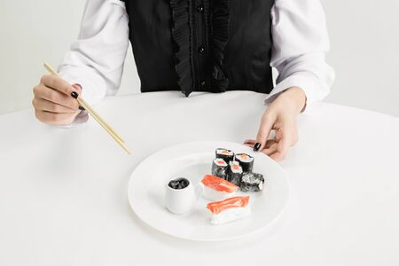 We are what we eat. Close up of womans eating plastic sushi, eco concept. There is so much polymers then were just made of it. Environmental disaster, fashion, beauty, food. Loosing organic world.