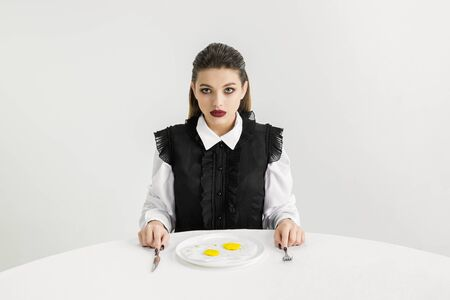 We are what we eat. Womans eating fried eggs made of plastic, eco concept. There is so much polymers then were just made of it. Environmental disaster, fashion, beauty, food. Loosing organic world.