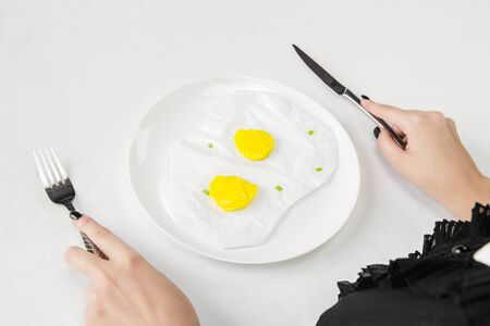 We are what we eat. Close up of womans eating fried eggs of plastic, eco concept. There is so much polymers then were just made of it. Environmental disaster, fashion, beauty. Loosing organic world.