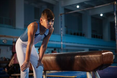 Little male gymnast training in gym, flexible and active. Caucasian fit little boy, athlete in white sportswear preparing for exercises for strength, balance. Movement, action, motion, dynamic concept. 写真素材