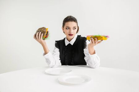 We are what we eat. Woman eats burger and hot-dog made of plastic, eco concept. There is so much polymers then were just made of it. Environmental disaster, fashion, beauty, food. Loosing organic.