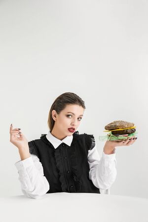 We are what we eat. Womans eating burger made of plastic, eco concept. There is so much polymers then were just made of it. Environmental disaster, fashion, beauty, food. Loosing organic world.