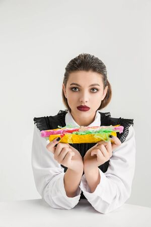 We are what we eat. Womans eating hot-dog made of plastic, eco concept. There is so much polymers then were just made of it. Environmental disaster, fashion, beauty, food. Loosing organic world.