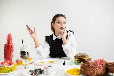 We are what we eat. Womans using smartphone against dishes made of plastic, eco concept. Ketchup, sushi, fried chicken, burger. Environmental disaster, fashion, beauty, food. Loosing organic world.