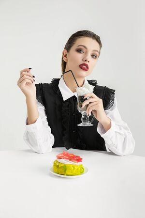Woman with cake and cocktail made of plastic, eco concept.