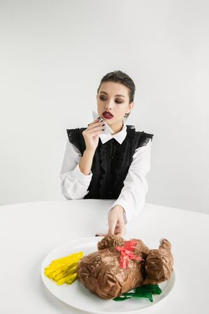 Woman eating fried chicken made of plastic, eco concept.