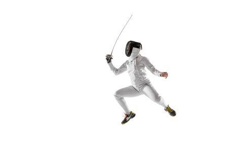 Tienermeisje in schermend kostuum met in hand zwaard dat op witte studioachtergrond wordt geïsoleerd. Jonge vrouwelijke Kaukasisch model oefenen en trainen in beweging, actie. Kopieerruimte. Sport, jeugd, gezonde levensstijl.