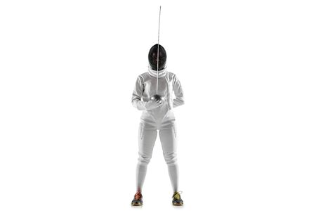 Teen girl in fencing costume with sword in hand isolated on white studio background. Young female caucasian model posing confident, preparing for fight. Copyspace. Sport, youth, healthy lifestyle.