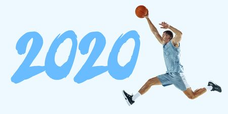 2020 Year meeting. Young caucasian basketball player in action, motion in jump isolated on blue background. Concept of sport, movement, energy and dynamic, healthy lifestyle. Training. Flyer for ad.