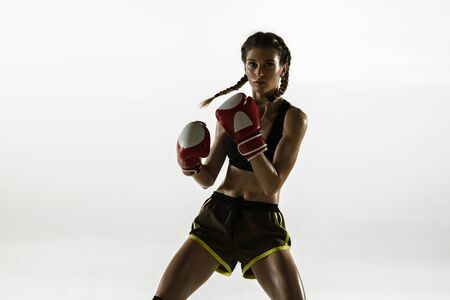 Fit caucasian woman in sportswear boxing isolated on white studio background. Novice female caucasian boxer training and practicing in motion and action. Sport, healthy lifestyle, movement concept.
