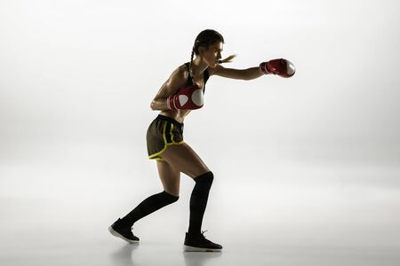Fit caucasian woman in sportswear boxing isolated on white studio background. Novice female caucasian boxer training and practicing in motion and action. Sport, healthy lifestyle, movement concept. Stock Photo
