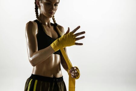Fit caucasian woman in sportswear boxing isolated on white studio background. Novice female caucasian boxer preparing for working out and training. Sport, healthy lifestyle, movement concept. Stock Photo
