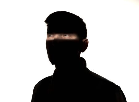 Portrait dramatique d'un jeune homme de race blanche dans le noir isolé sur fond de studio blanc. Ligne de lumière du soleil sur le visage sombre. Nature humaine, choses cachées, concept de psychologie. Photo créative élégante d'art.