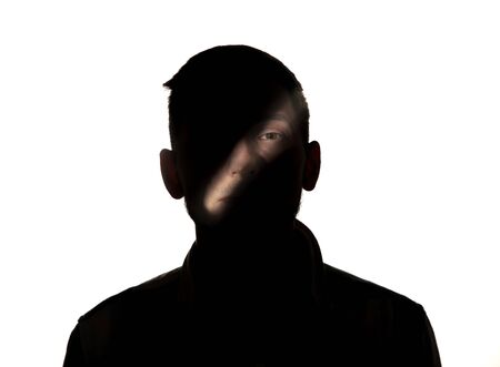 Dramatic portrait of caucasian young man in the dark isolated on white studio background. Sunlight line on the dark face. Human nature, hidden things, psycology concept. Art elegant creative photo. 写真素材