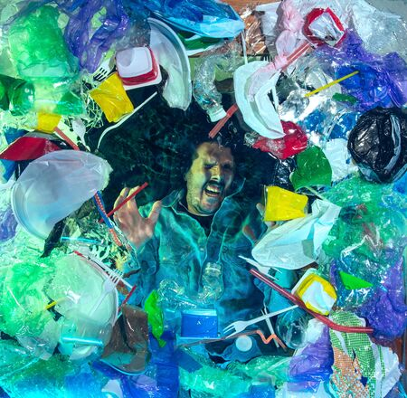 Man drowning in water under plastic recipients pile, garbage. Used bottles and packs filling world ocean killing people. Ecology, environment concept, plastic and glass pollution, nature disaster.