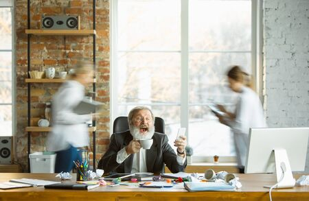 Tired boss resting at his workplace while busy people moving near blurred. Office worker, manager working, drinking coffee and giving directions for his colleagues. Business, work, workload concept.