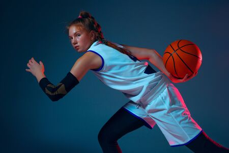 Flexibility. Young caucasian female basketball player on blue studio background in neon light, motion and action. Concept of sport, movement, energy and dynamic, healthy lifestyle. Training, practicing.