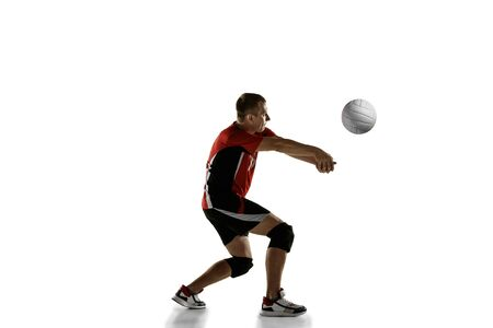Young caucasian volleyball player placticing isolated on white background. Male sportsman training with the ball in motion and action. Sport, healthy lifestyle, activity, movement concept. Copyspace.