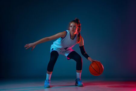 Movement. Young caucasian female basketball player on blue studio background in neon light, motion and action. Concept of sport, movement, energy and dynamic, healthy lifestyle. Training, practicing. Foto de archivo - 135358214