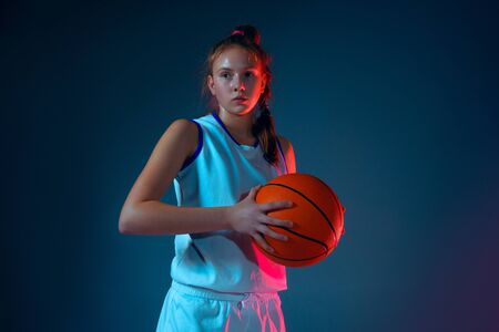 Strength.Young caucasian female basketball player on blue studio background in neon light, motion and action. Concept of sport, movement, energy and dynamic, healthy lifestyle. Posing confident. Foto de archivo - 135358218