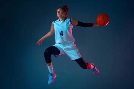 Target. Young caucasian female basketball player on blue studio background in neon light, motion and action. Concept of sport, movement, energy and dynamic, healthy lifestyle. Training, practicing. Foto de archivo - 135358248
