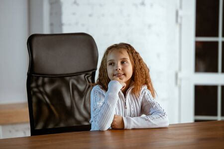 Portrait of young caucasian girl in casual clothes looks dreamful, cute and happy. Looking up and thinking, sitting indoors at the wooden table. Concept of future, target, dreams, visualisation. Zdjęcie Seryjne