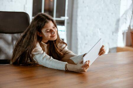 Porträt des jungen kaukasischen Mädchens sieht verträumt, süß und glücklich aus. Nach oben schauen, drinnen am Holztisch mit Tablet und Smartphone sitzen. Zukunftskonzept, Ziel, Kauftraum, Visualisierung.