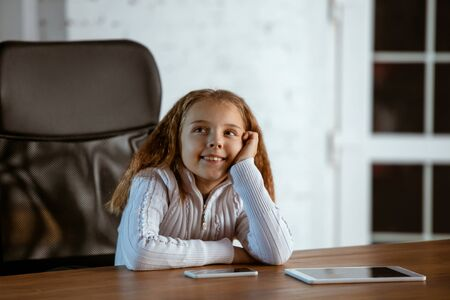 Portrait of young caucasian girl looks dreamful, cute and happy. Looking up, sitting indoors at the wooden table with tablet and smartphone. Concept of future, target, dream to buy, visualisation.