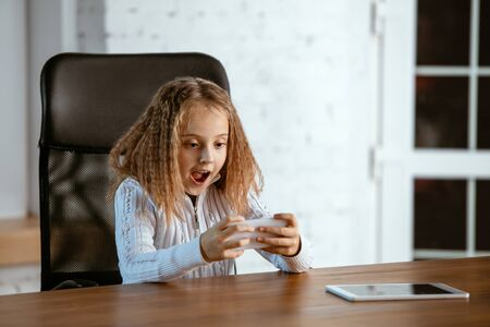 Portrait of young caucasian girl in looks dreamful, cute and happy. Astonished sitting indoors at the wooden table with tablet and smartphone. Concept of future, target, dream to buy, visualisation.