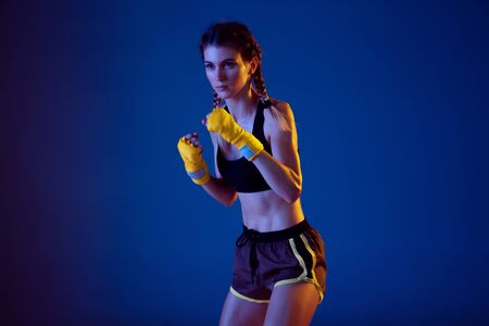 Natural. Fit caucasian woman in sportswear boxing on blue studio background in neon light. Novice female caucasian boxer working out and training. Sport, healthy lifestyle, movement concept.