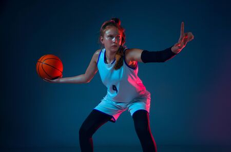 A moment. Young caucasian female basketball player on blue studio background in neon light, motion and action. Concept of sport, movement, energy and dynamic, healthy lifestyle. Training, practicing. Foto de archivo - 135358381