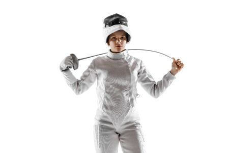 Teen girl in fencing costume with sword in hand isolated on white studio background. Young female caucasian model practicing and training in motion, action. Copyspace. Sport, youth, healthy lifestyle.