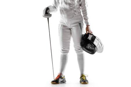 Close up van tiener meisje in schermen kostuum met zwaard in de hand geïsoleerd op een witte studio achtergrond. Jong vrouwelijk Kaukasisch model in beweging, actie. Zelfverzekerd. Kopieerruimte. Sport, jeugd, gezonde levensstijl.