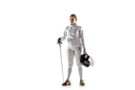 Teen girl in fencing costume with sword in hand isolated on white studio background. Young female caucasian model in motion, action. Posing confident. Copyspace. Sport, youth, healthy lifestyle.