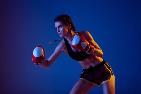 Motion. Fit caucasian woman in sportswear boxing on blue studio background in neon light. Novice female caucasian boxer working out and training. Sport, healthy lifestyle, movement concept.