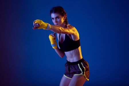 Kicking. Fit caucasian woman in sportswear boxing on blue studio background in neon light. Novice female caucasian boxer working out and training. Sport, healthy lifestyle, movement concept.