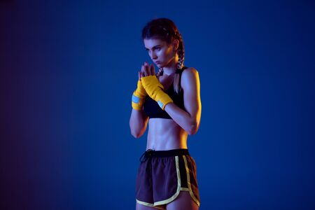 Fit caucasian woman in sportswear boxing on blue studio background in neon light. Novice female caucasian boxer preparing for working out and training. Sport, healthy lifestyle, movement concept.
