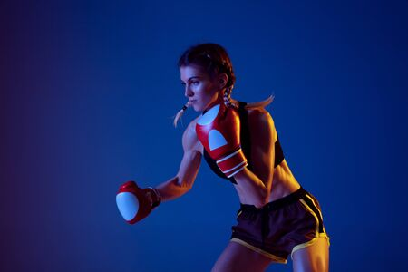 Confidence. Fit caucasian woman in sportswear boxing on blue studio background in neon light. Novice female caucasian boxer working out and training. Sport, healthy lifestyle, movement concept.